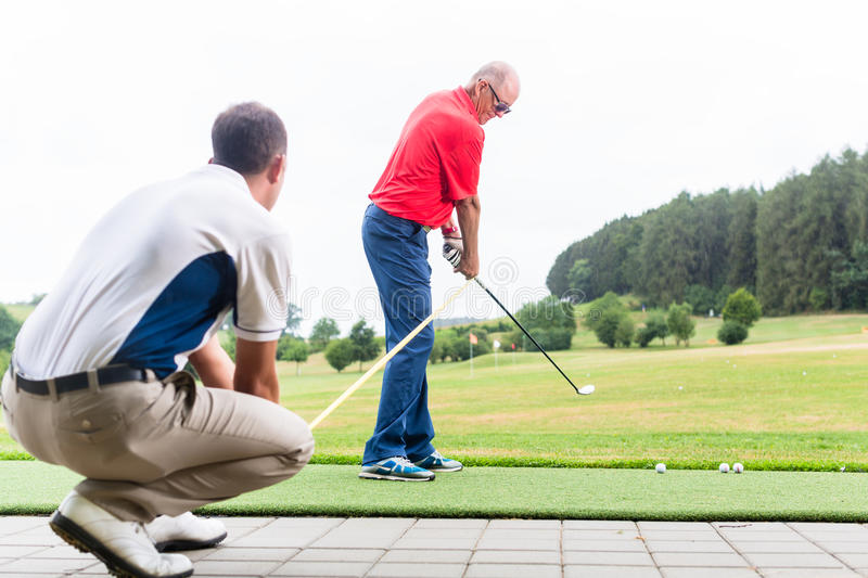Golf trainer working with golf player on driving range stock image
