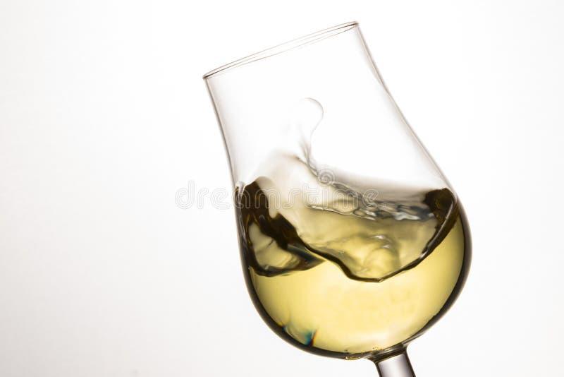 Golf van witte wijn in een overgeheld glas royalty-vrije stock foto's