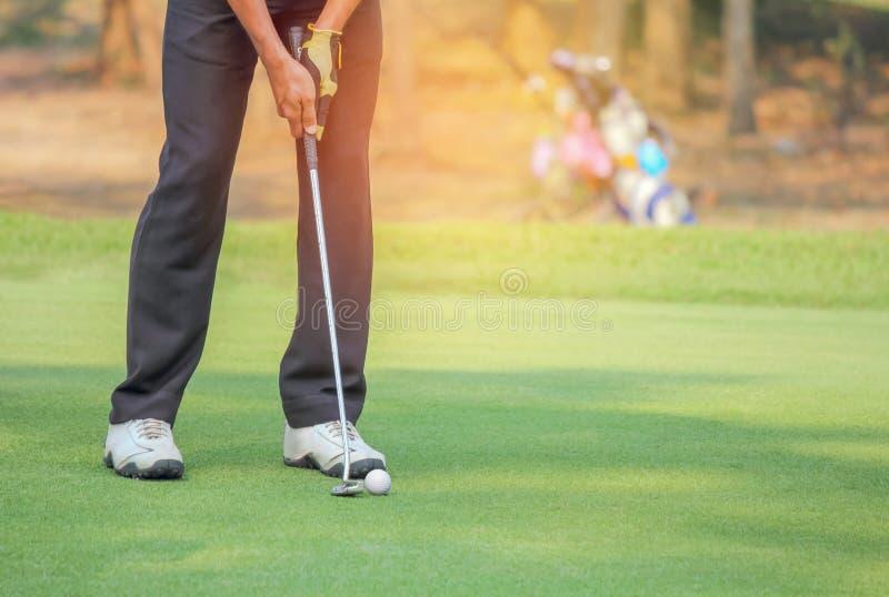 Golfare i handling som sätter golfboll på det gröna gräset nära hålet royaltyfria bilder