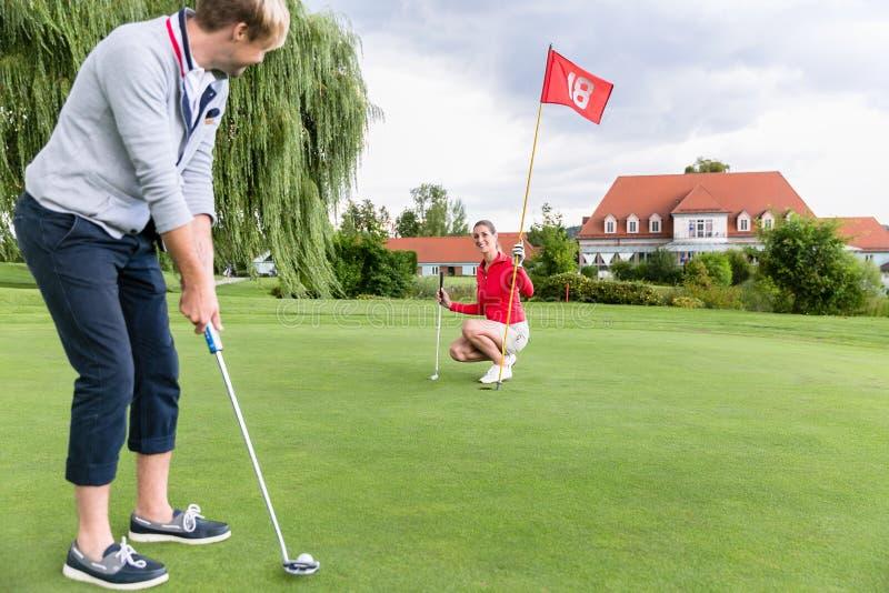 Golfare på sättande grönt omkring som tar skottet arkivbilder