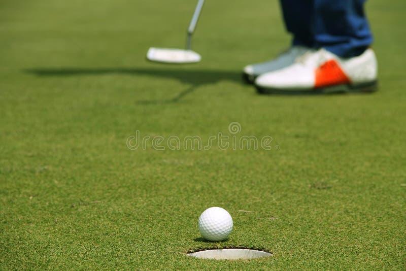 Golfare som s?tter golfboll p? den gr?na golfen royaltyfria foton
