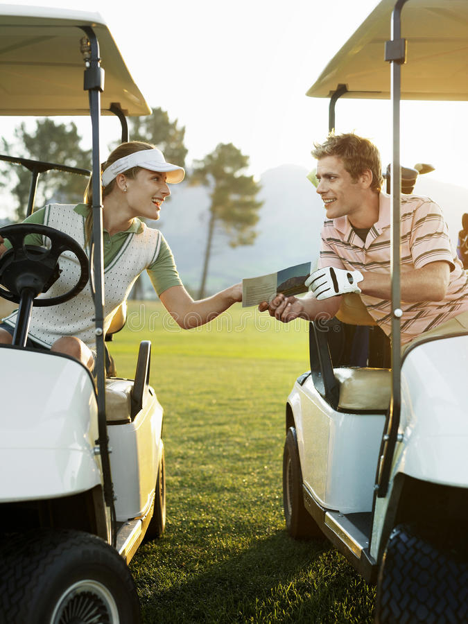Golfare som sitter i golfvagnar som rymmer ställningkortet arkivfoto