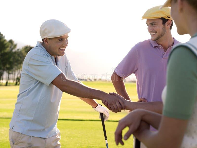 Golfare som skakar händer på golfbana arkivbilder