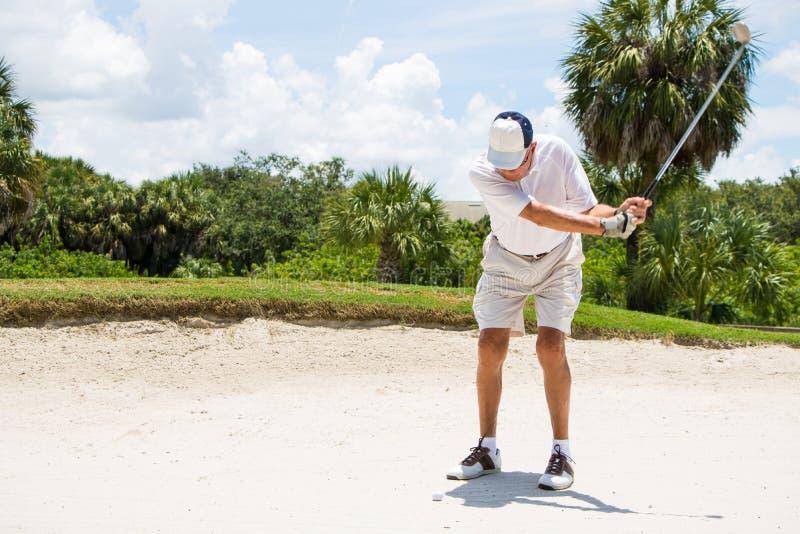 Golfare som slår bollen från sand royaltyfri fotografi