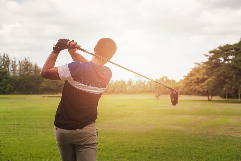 Golfare som slår golfskottet med klubban på kurs på aftontid royaltyfria bilder