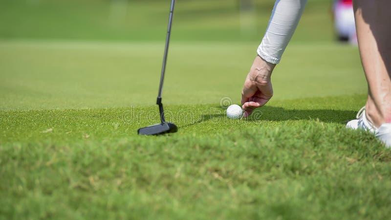 Golfaren skjuter golfboll av golfklubben fr?n utslagsplatsaskar p? golfbanan i konkurrenslek arkivbilder