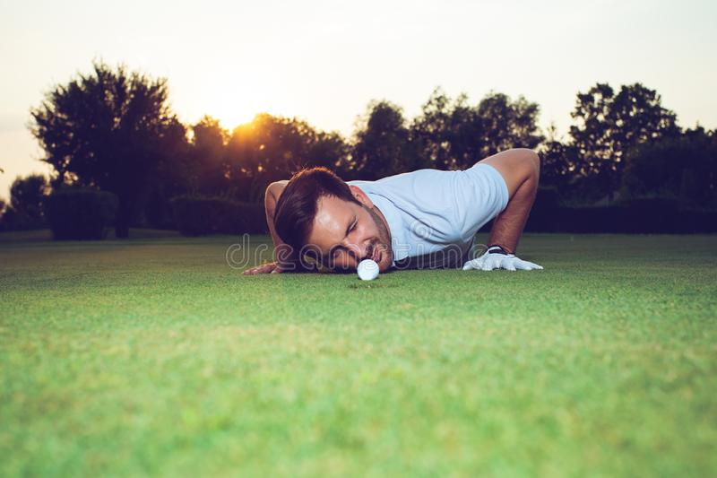 Golfaren som kontrollerar linjen av, sätter på gräsplan royaltyfria bilder
