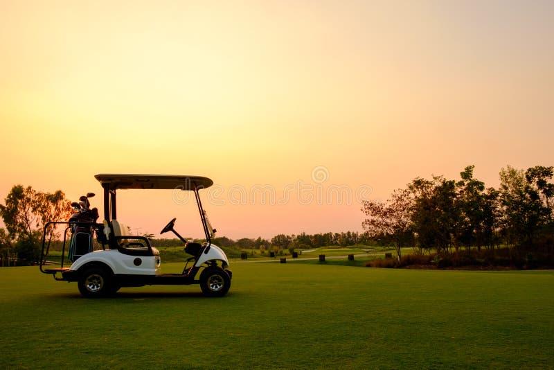 Golfauto in een vaarbaan op een golfbaan met vers groen grasveld en wolkenhemel stock fotografie