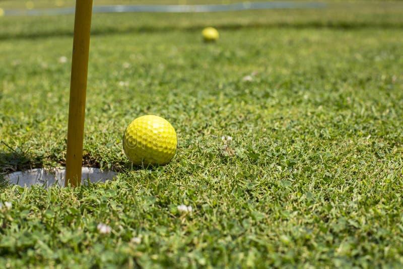 Golfbal dichtbij het gat stock afbeelding