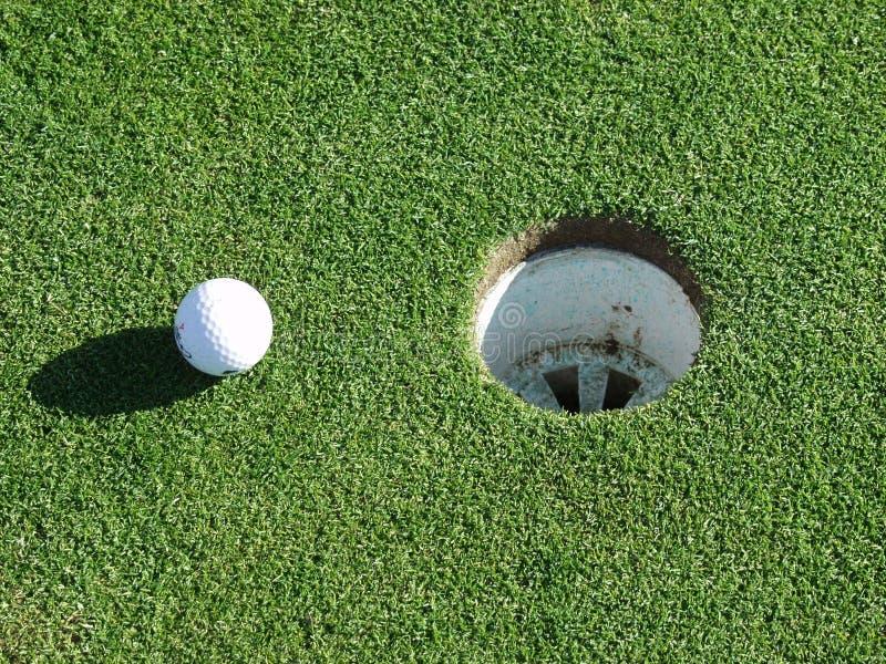 Golfbal en gat royalty-vrije stock afbeeldingen