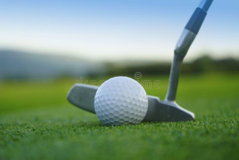 Golfbal en golfclub in mooie golfcursus bij zonsondergang backg stock fotografie