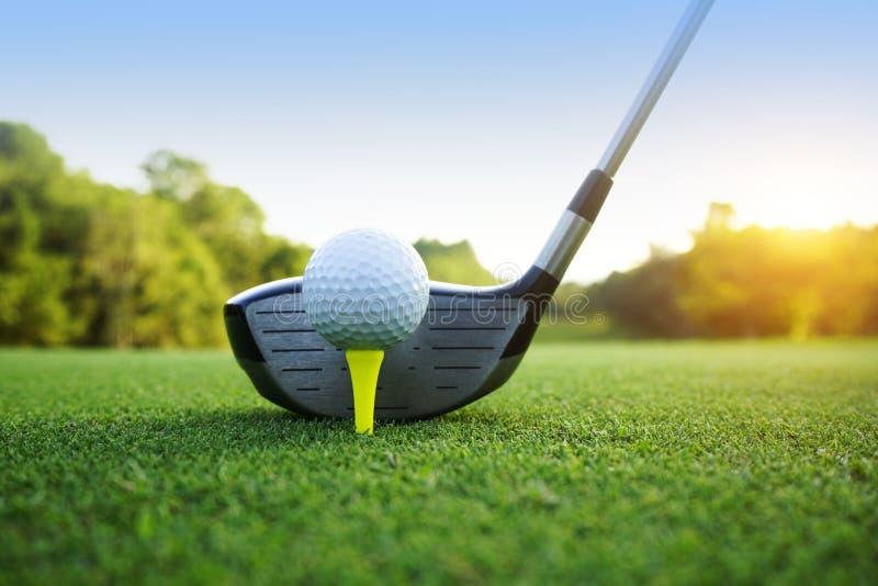Golfbal en golfclub in mooie golfcursus met zonsondergangbac stock afbeelding