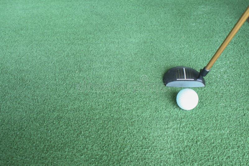 Golfbal en putter op groen gras stock afbeeldingen