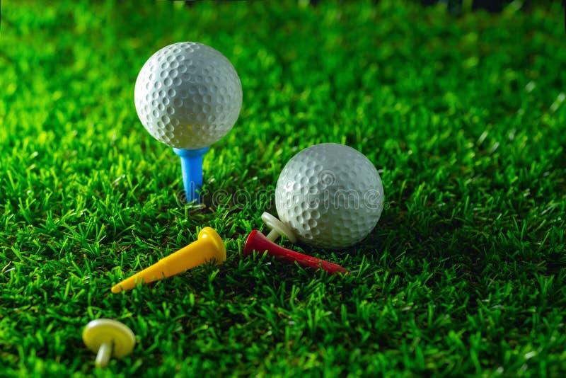 Golfbal en T-stuk op gras royalty-vrije stock foto's