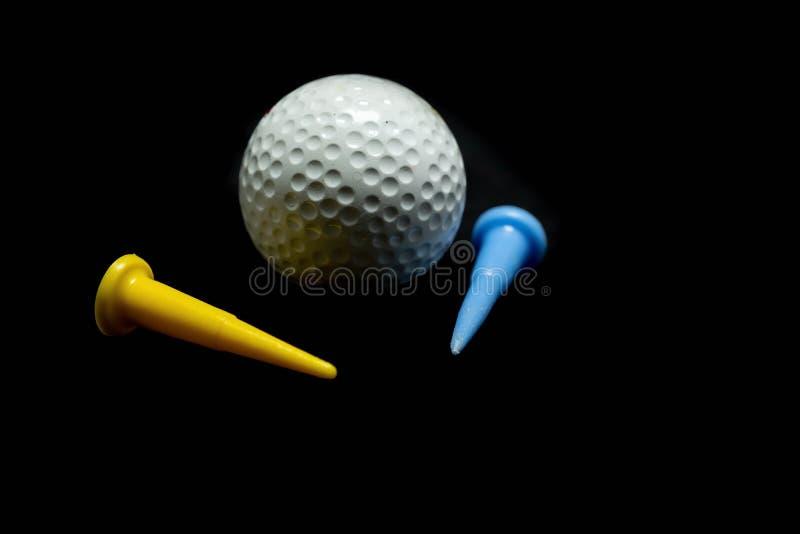 Golfbal en T-stuk op zwarte achtergrond stock afbeelding