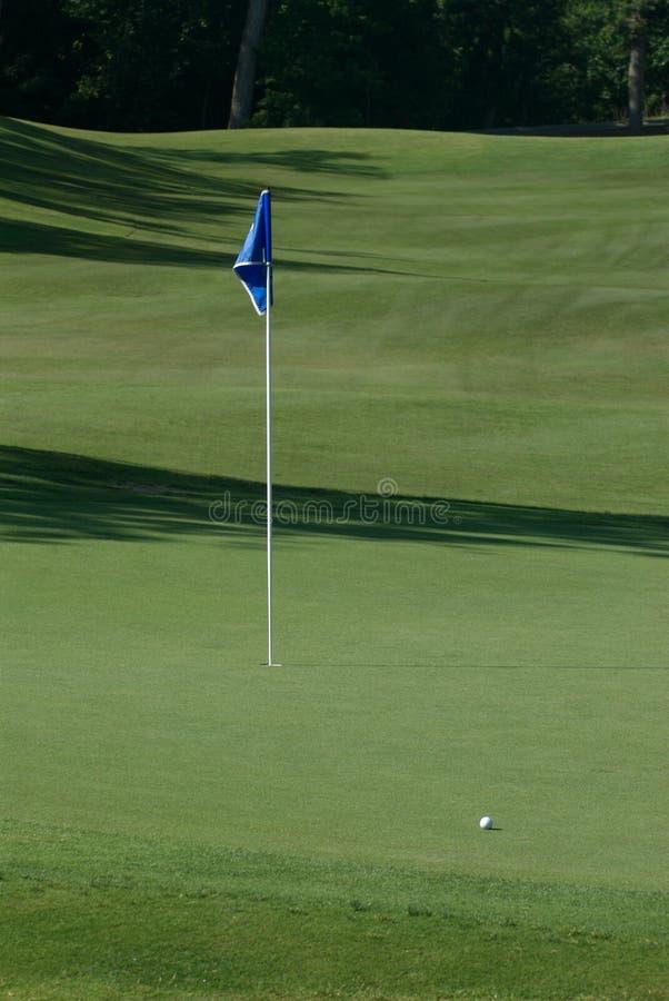 Golfbal en vlag op groen stock foto's