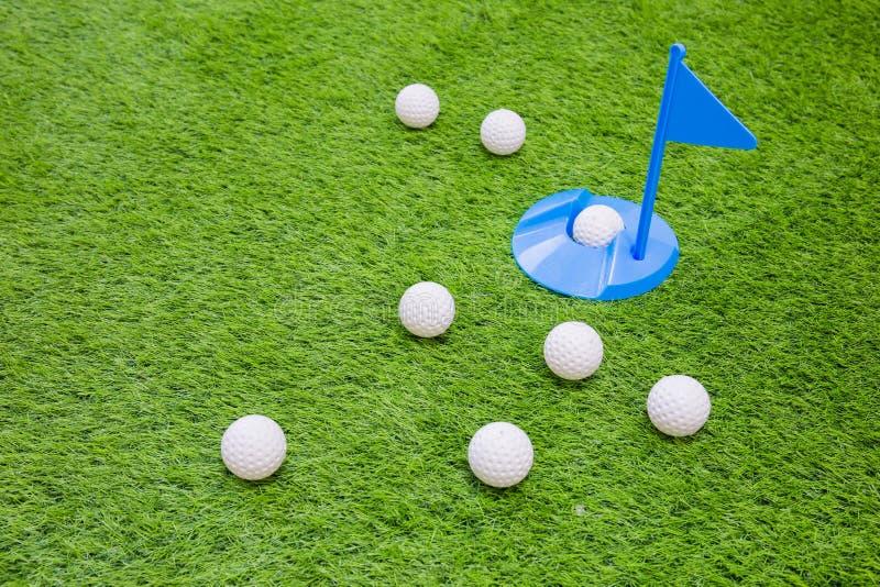 Golfbal met in gat op gras royalty-vrije stock fotografie