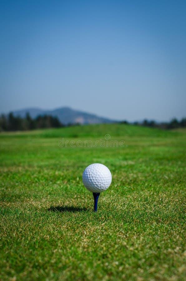 Golfbal op het teeing gebied met groen gras vooruit en bergen binnen royalty-vrije stock afbeeldingen