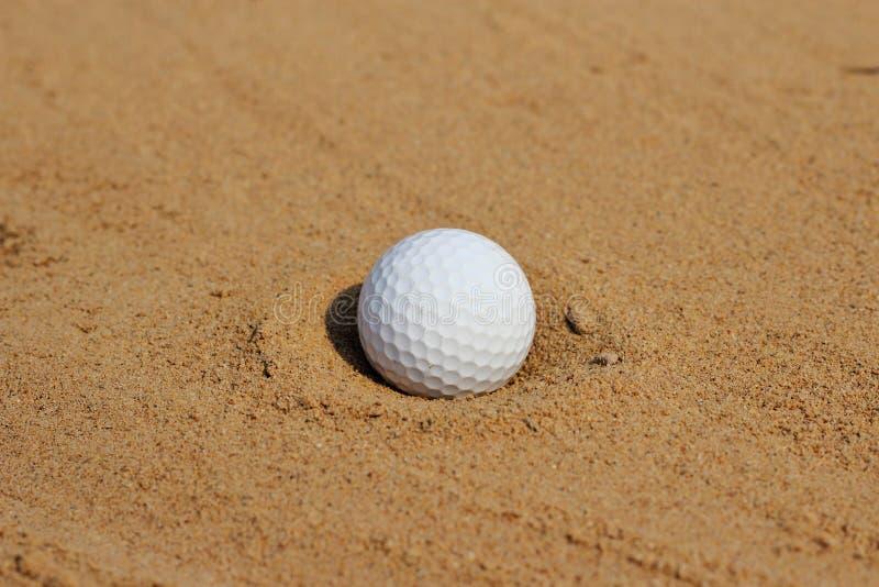 golfbal in zand op bunker stock afbeelding