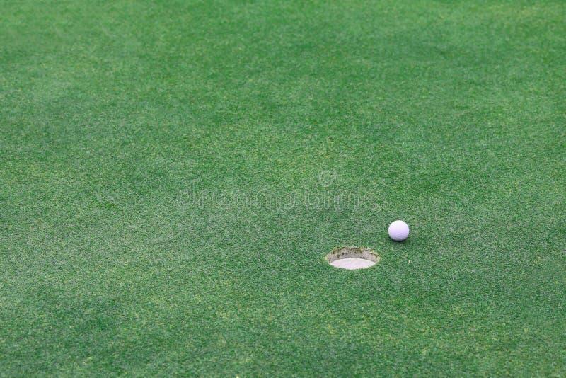 Golfball auf Lippe von Cup lizenzfreies stockbild