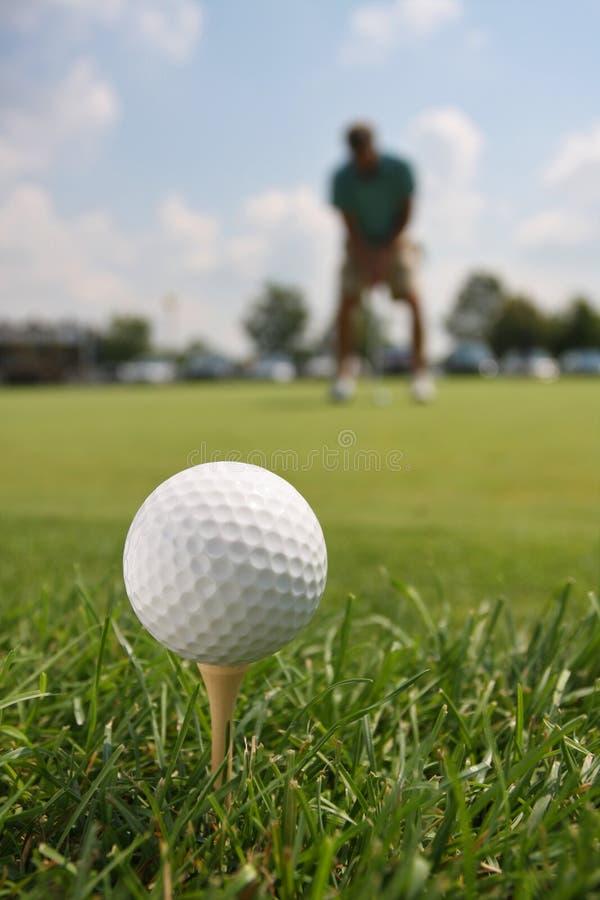 Golfball auf T-Stück mit Golfspieler lizenzfreie stockfotos