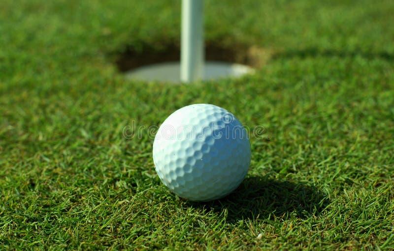 Golfball davanti al foro fotografia stock libera da diritti