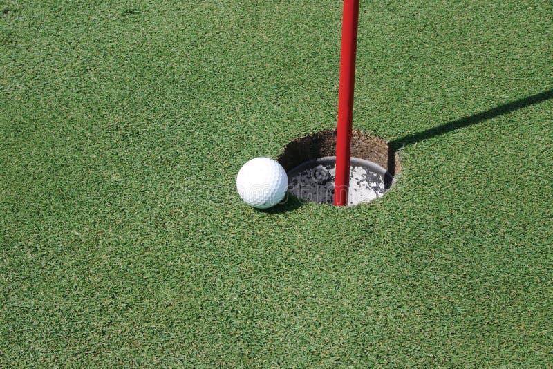 Golfball durch das Loch stockfotografie