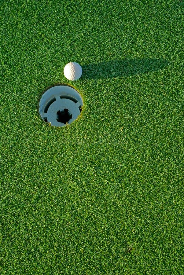 Golfball ein nahe bei Loch 4 lizenzfreie stockfotografie