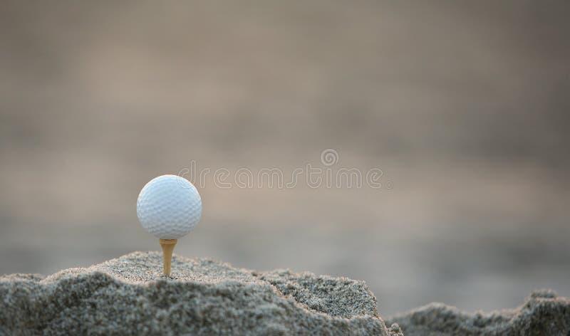 Golfball im Sand stockfotos