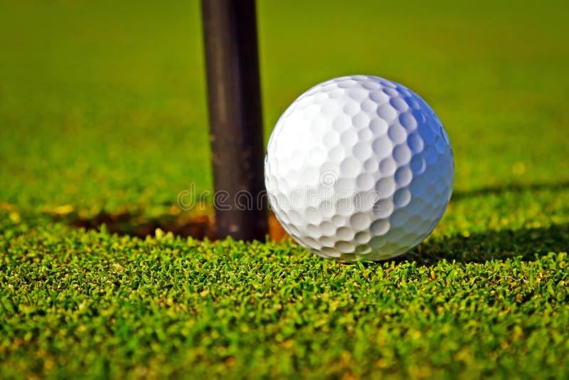 Golfball nahe dem Loch lizenzfreie stockbilder