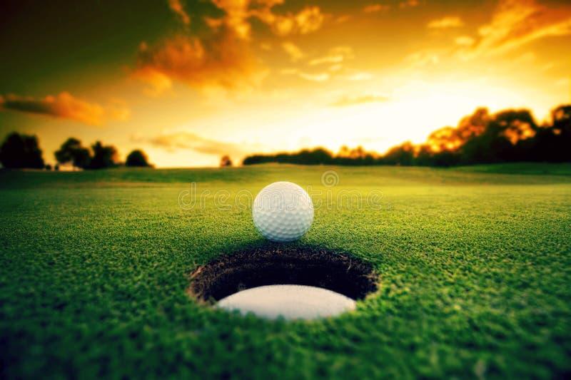 Golfball nahe Loch lizenzfreie stockbilder