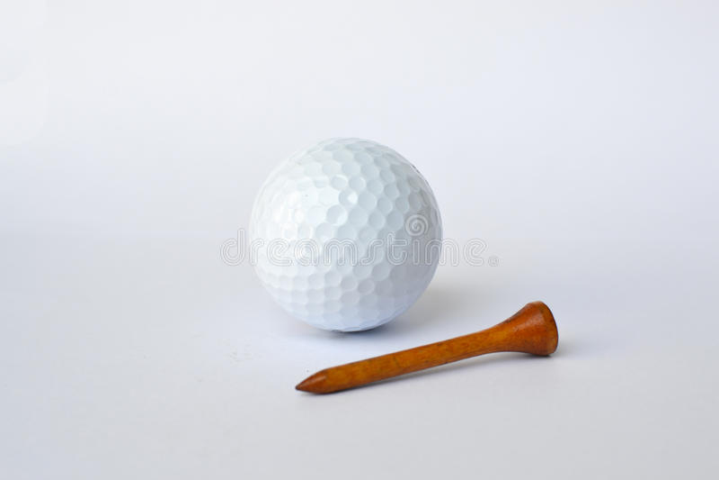 Golfball und hölzernes T-Stück stockbild