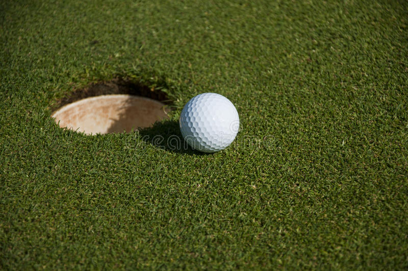 Golfball und Loch lizenzfreie stockbilder