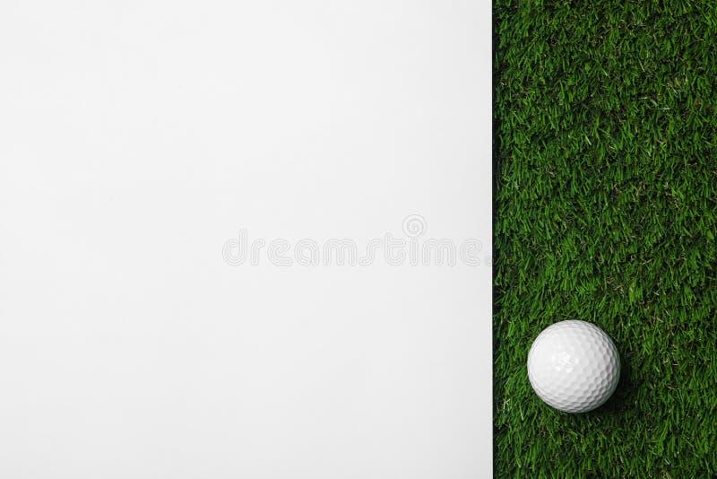 Golfball- und Weißbuch auf grünem künstlichem Gras, Raum für Text stockfoto