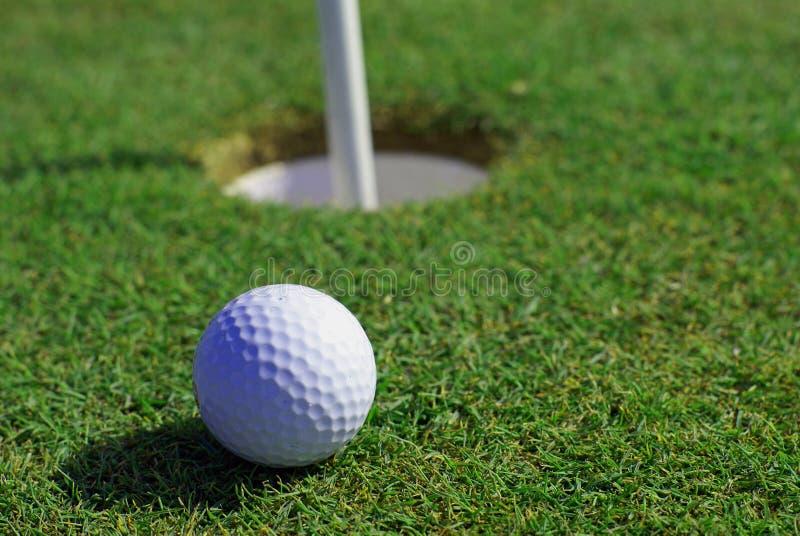 Golfball vor dem Loch lizenzfreie stockfotos