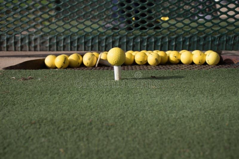 Golfballball auf einem T-Stück stockfotos