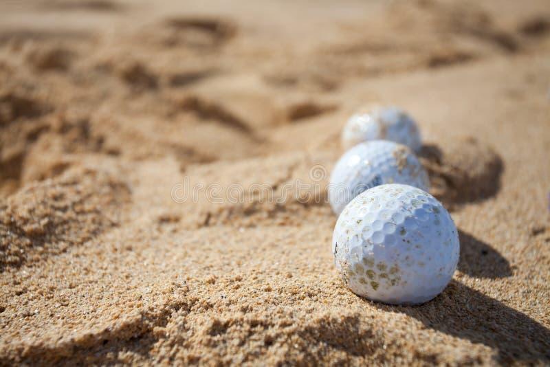 Golfballen in een zand stock fotografie