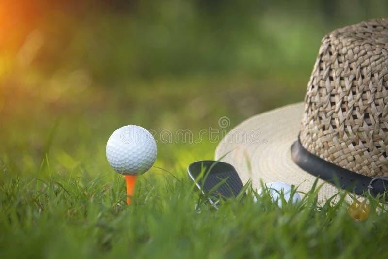Golfballen en golfclubs evenals materiaal worden gebruikt om golf op groen gras te spelen dat stock foto