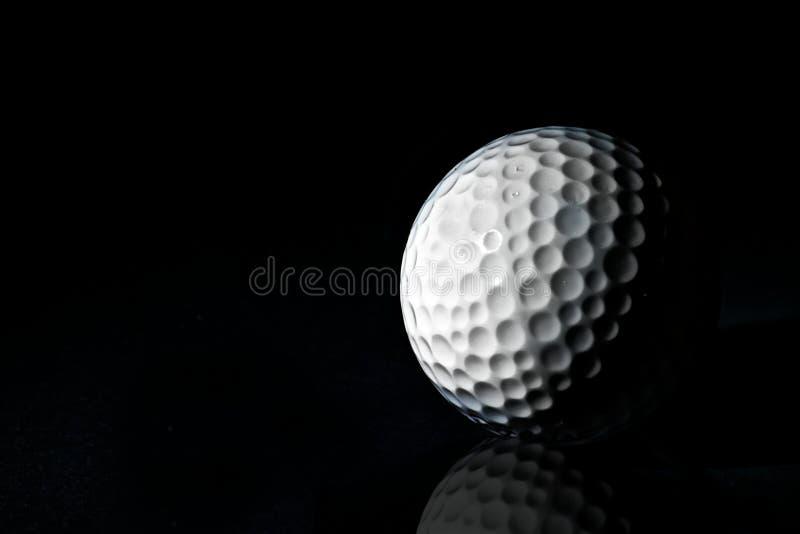 Golfballs su fondo nero immagini stock
