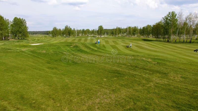 Golfbana för flyg- sikt Golfare som går ner farleden på en kurs med den golfpåsen och spårvagnen arkivbilder