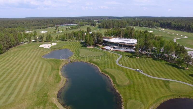 Golfbana på en solig dag, en utmärkt golfklubb med damm och grönt gräs, sikt från himlen royaltyfria bilder