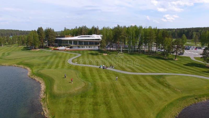 Golfbana på en solig dag, en utmärkt golfklubb med damm och grönt gräs, sikt från himlen arkivbild