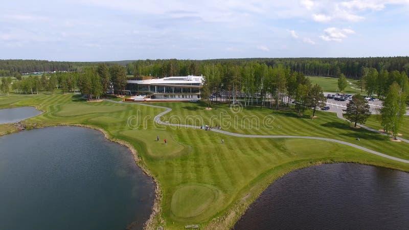 Golfbana på en solig dag, en utmärkt golfklubb med damm och grönt gräs, sikt från himlen royaltyfri bild