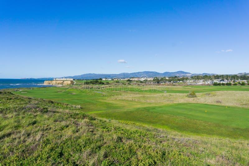 Golfbana på klipporna av Stilla havetkusten, semesterorten och villorna i bakgrunden, Half Moon Bay, Kalifornien arkivbild