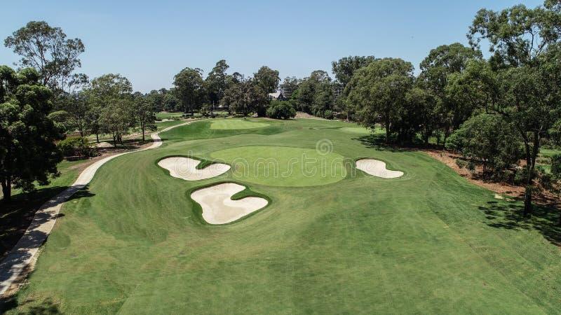 Golfbanafarled och gräsplan med sandbunkerfaror som omges av träd mot blå himmel arkivbild