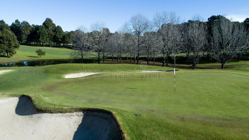 Golfbanagräsplan med flaggan, bunker, fördämningen och trädet fodrade farleden arkivbilder