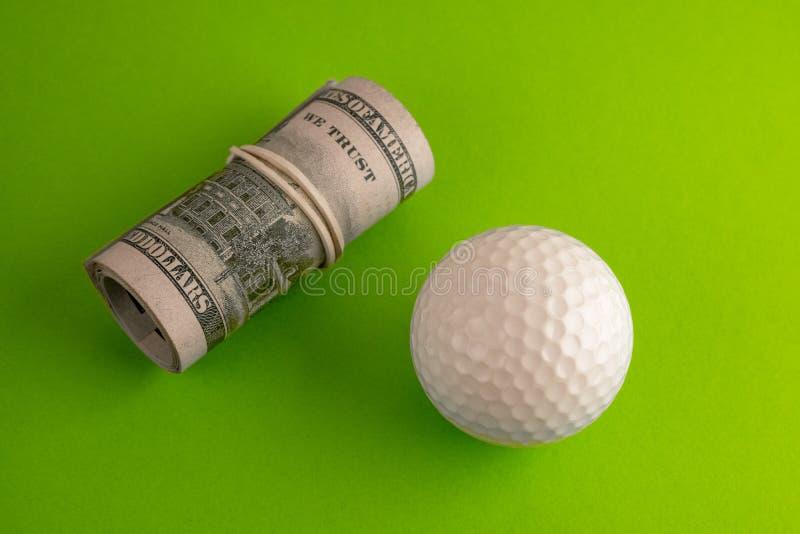 Golfboll bredvid en rulle av hundra dollarräkningar av USA med en vit gummiband Grön bakgrund Begreppet av sportar royaltyfri foto