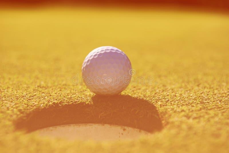 Golfboll i hålet royaltyfria bilder