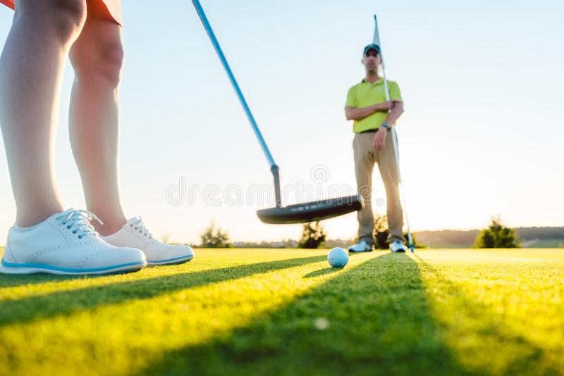 Golfboll i selektiv fokus under putterklubban av en kvinnlig spelare arkivbilder