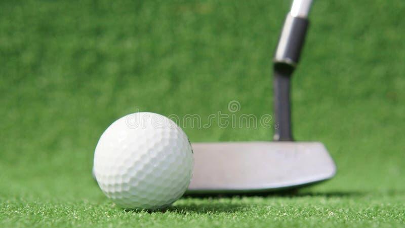 Golfboll med putter i bakgrunden på gröngräs arkivfoto